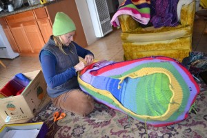 Rainbow sewing felted knit sheets over willow armature.