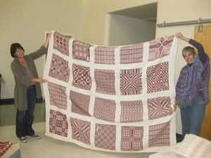 Therese May and Jan DeShera with quilt top.