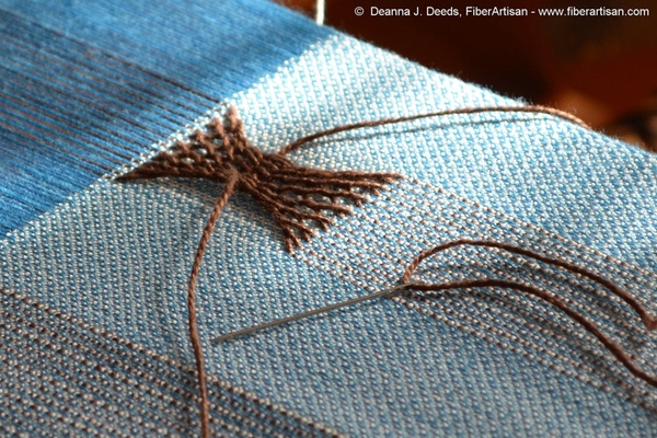 Blue fabric on the loom with warp sprang hourglass motif in brown