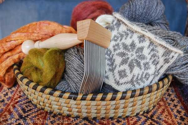 Basket with wool comb, spinning fibers, gray yarn, and a white and gray stranded knitting swatch in a star pattern. The basket is on a multicolor diamond twill mat.