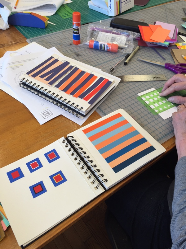 A person designing a project with books of color samples and color scheme examples